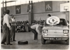 Wymiana koła w samochodzie fiat 126p podczas Turnieju Rodzin, zorganizowanego przy współpracy Obornickiego Ośrodka Kultury w hali sportowej OSiR, 20.03.1983 r. [Dokument ikonograficzny]