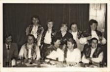 Zdjęcie zespołu śpiewaczego z Piekar z Haliną Pietrzak (stoi trzecia z lewej), dyrektor Obornickiego Ośrodka Kultury, po występie dla seniorów z okazji Dnia Seniora, listopad 1985 r. [Dokument ikonograficzny]